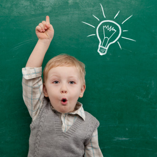 Kid thinking w light bulb on blackboard