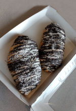 Chocolate croissants drizzled with powdered sugar in a take out box